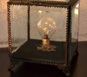 Carved drug, wooden base, globe-bulb on silver wire in an old glass and brass box • 12x15,5x12cm • More pic. GALLERY SCULPTURES